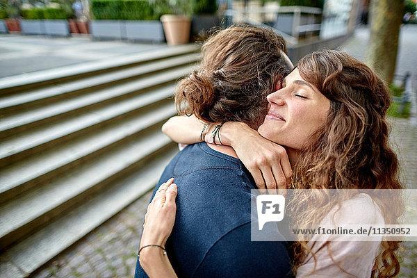 Glückliches junges Paar umarmt sich in der Stadt
