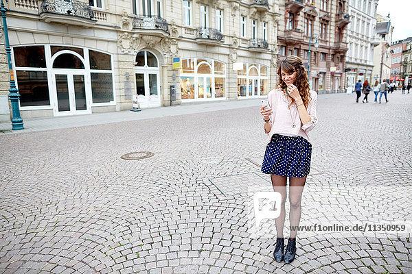 Lächelnde junge Frau in der Stadt schaut auf ihr Handy