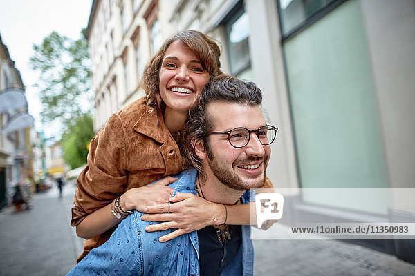 Junger Mann trägt seine Freundin huckepack in der Stadt
