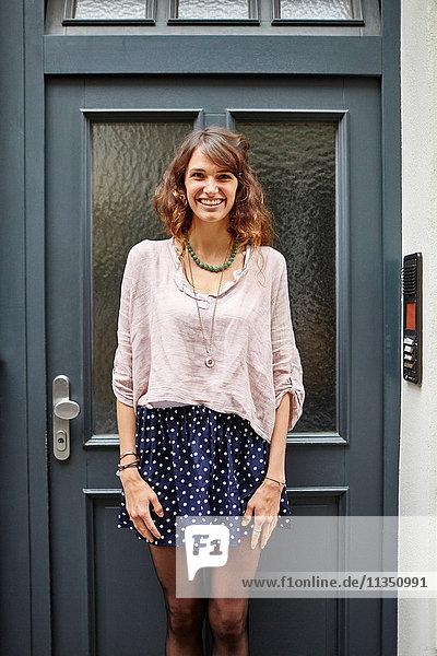 Portrait einer lächelnden jungen Frau an einer Tür