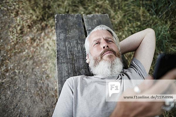 Reifer Mann mit Vollbart liegt auf einer Bank mit Handy