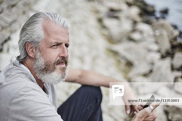 Reifer Mann mit Vollbart sitzt mit Handy am Flussufer