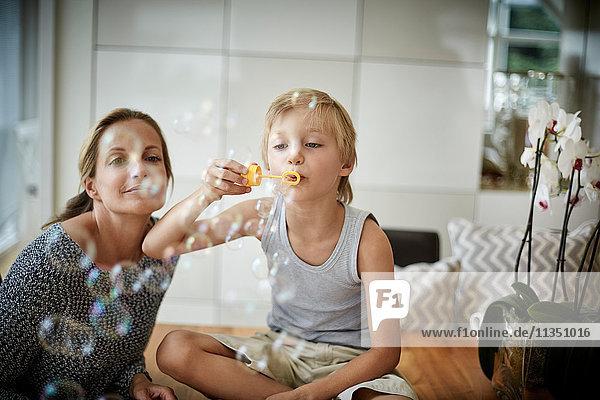 Junge mit Mutter macht Seifenblasen