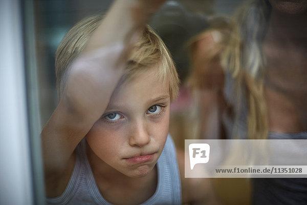 Ernster Junge schaut aus dem Fenster