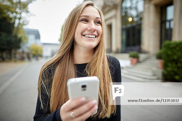 Lächelnde junge Frau mit Handy im Freien
