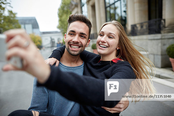 Fröhliches junges Paar macht ein Selfie im Freien