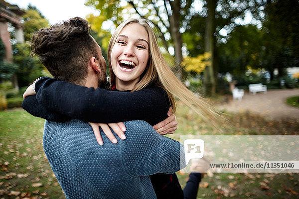 Fröhliches junges Paar umarmt sich im Park