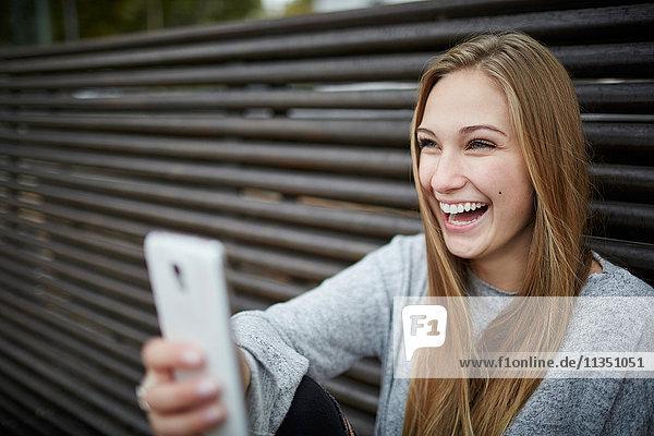 Fröhliche junge Frau mit Handy im Freien