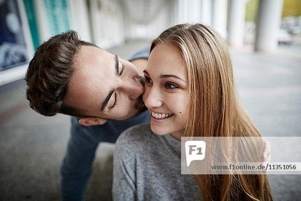 Glückliches junges Paar küsst sich im Freien