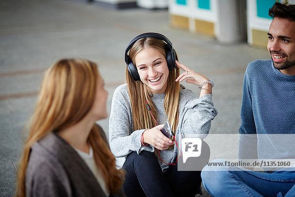 Fröhliche junge Frau mit Kopfhörern sitzt mit Freunden zusammen