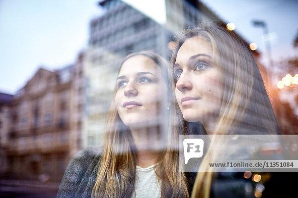 Zwei lächelnde junge Frauen schauen durchs Fenster