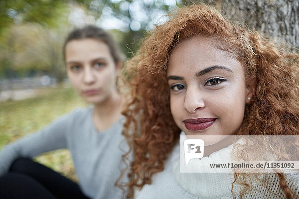 Portrait of teenage girl with friend in park