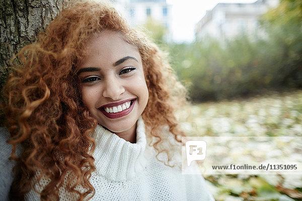 Portrait einer lächelnden Teenagerin im Park