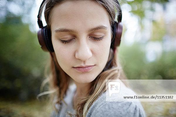 Junge Frau mit geschlossenen Augen und Kopfhörern