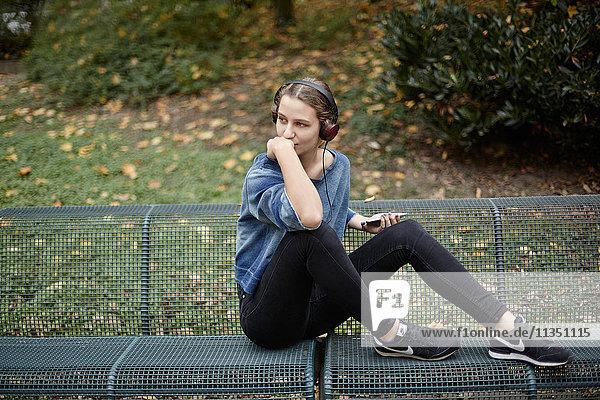Junge Frau mit Kopfhörern auf einer Parkbank