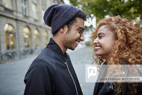 Lächelndes junges Paar schaut sich an