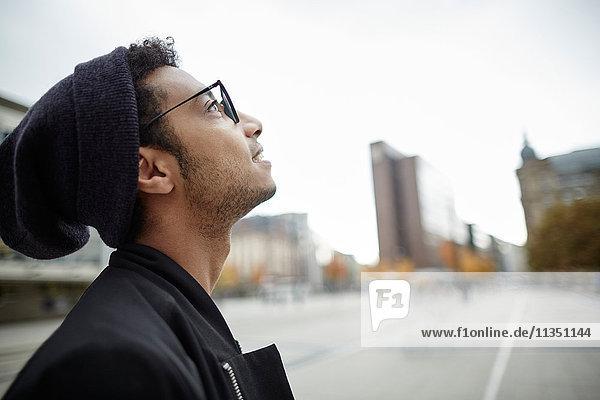 Junger Mann im Freien schaut nach oben