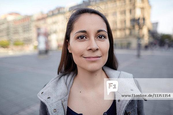 Portrait einer lächelnden Frau in der Stadt