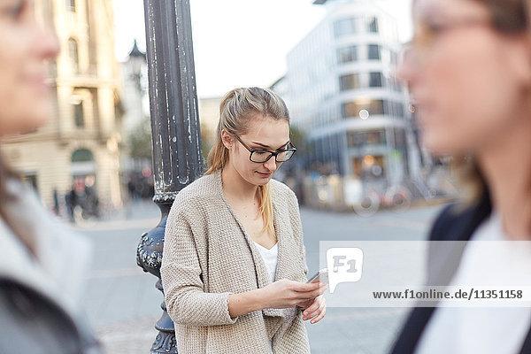 Frau schaut auf ihr Handy in der Stadt mit zwei Frauen im Vordergrund