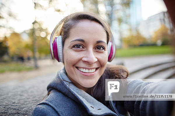 Portrait of smiling woman wearing headphones outdoors