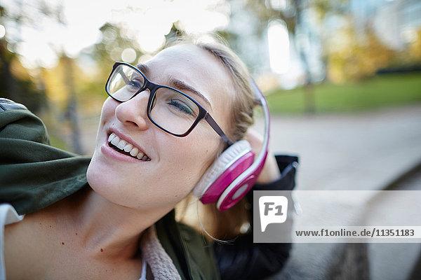 Fröhliche Frau mit Kopfhörern im Freien