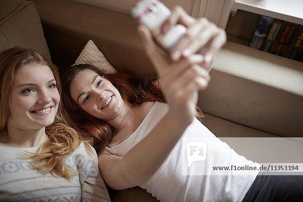 Zwei junge Frauen liegen auf der Couch und machen ein Selfie