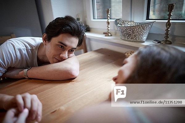 Verliebtes junges Paar sitzt Zuhause am Tisch und schaut sich an