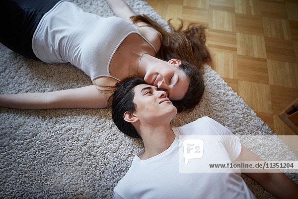 Junges Paar liegt auf einem Teppich auf dem Fußboden