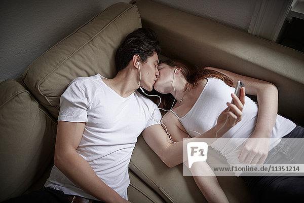 Junges Paar liegt auf der Couch  hört Musik und küsst sich