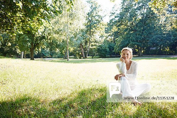 Lächelnde reife Frau sitzt auf einer Wiese im Park