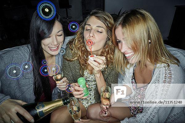 Drei fröhliche Frauen sitzen auf der Couch mit Sekt und machen Seifenblasen