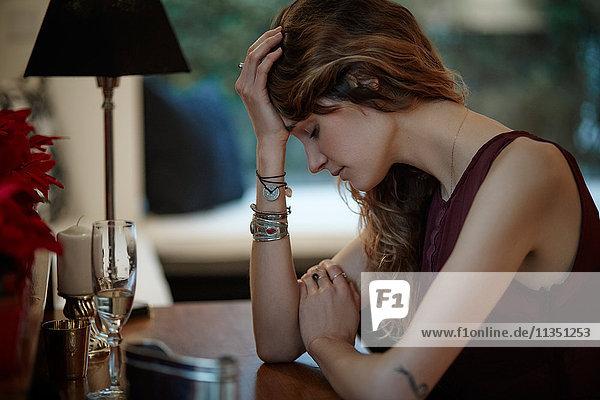 Ernste junge Frau sitzt am Tisch mit dem Kopf in der Hand
