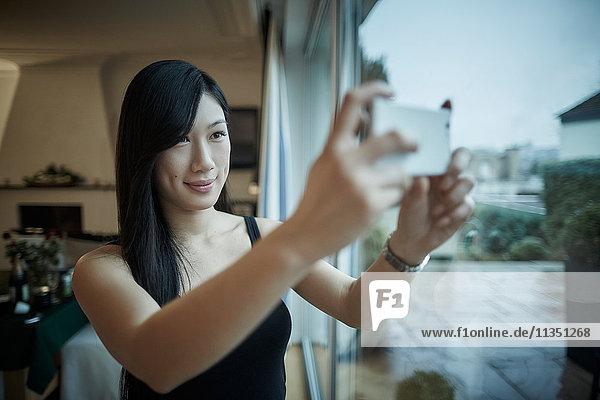 Junge Frau macht ein Selfie am Fenster