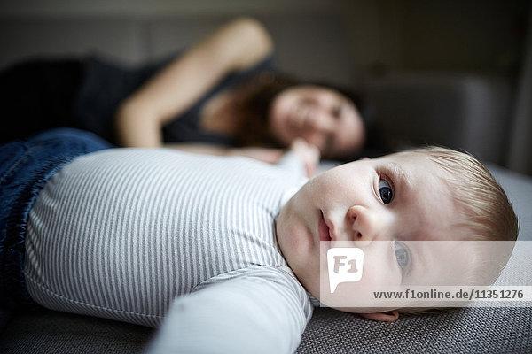 Baby liegt auf der Couch mit Mutter im Hintergrund