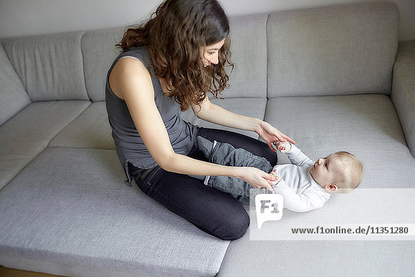 Fröhliche Mutter spielt mit Baby auf der Couch