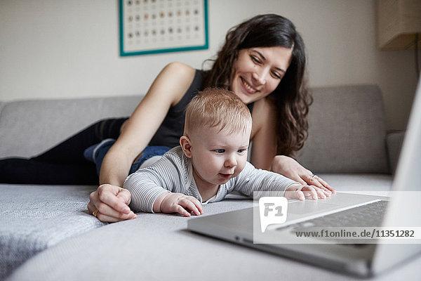 Mutter mit Baby und Laptop auf der Couch