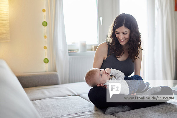 Mother and baby sitting on couch