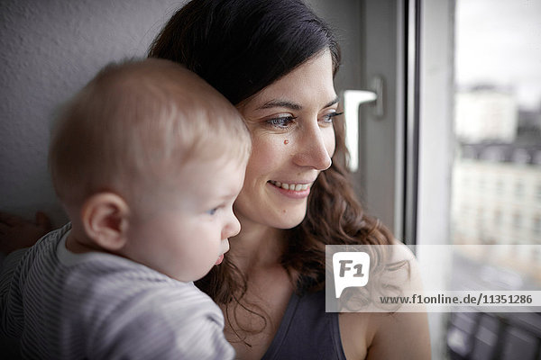 Mother and baby looking out of window