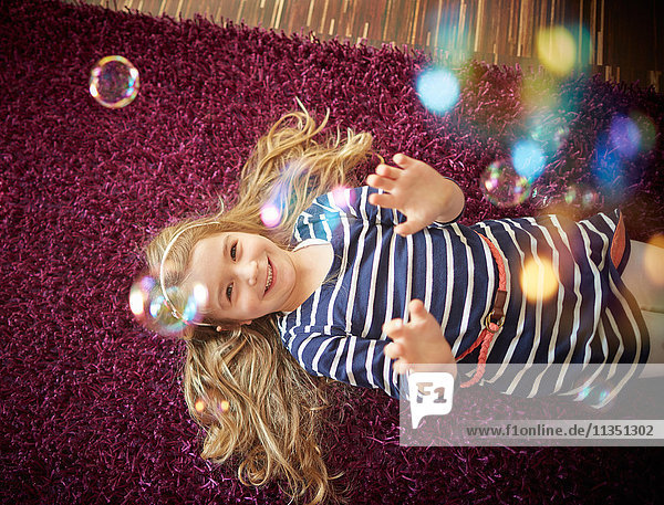 Happy girl lying on carpet playing with soap bubbles