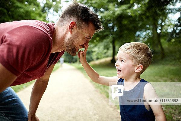 Fröhlicher Junge berührt Vaters Nase