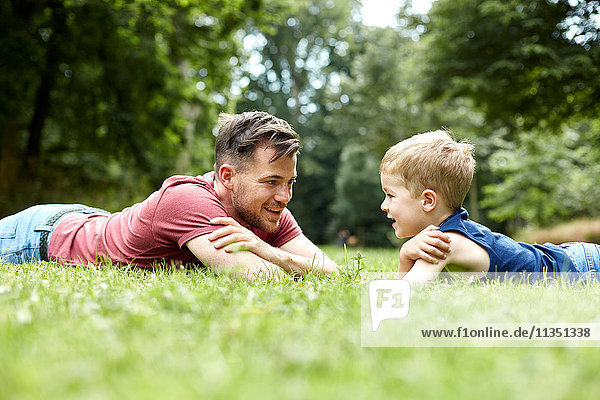 Father and son lying face to face in meadow