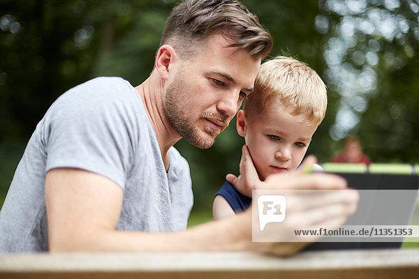 Vater und Sohn schauen auf Tablet