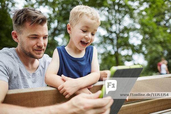 Vater und fröhlicher Sohn schauen auf Tablet