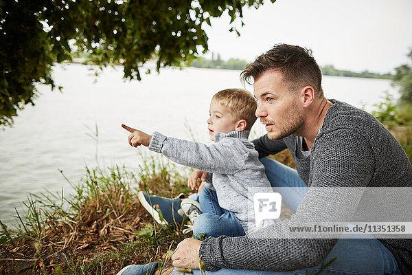 Sohn sitzt mit Vater am Flussufer und deutet auf etwas