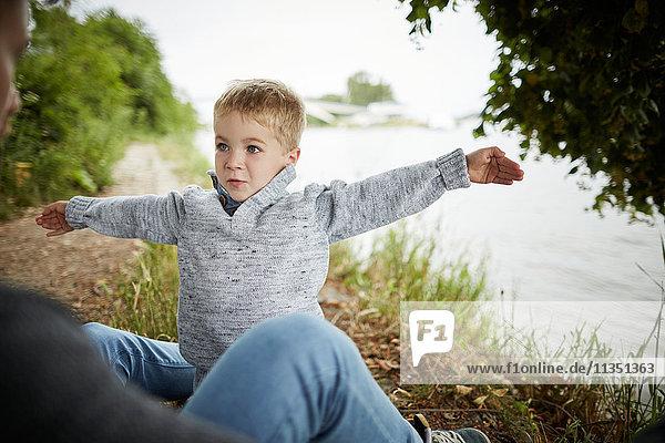 Sohn mit ausgebreiteten Armen am Flussufer schaut auf Vater