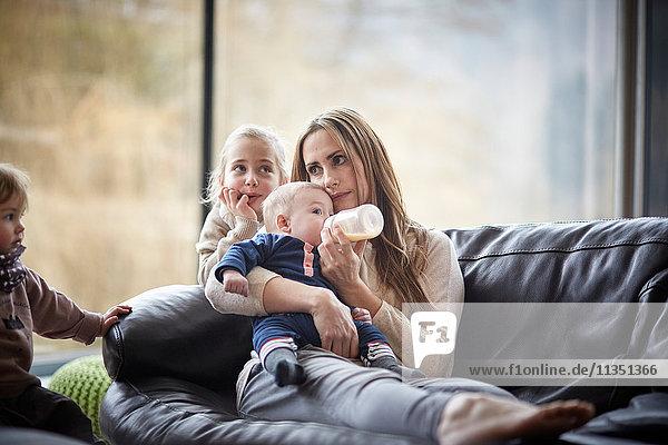 Mutter mit drei Kindern gibt ihrem Baby das Fläschchen auf der Couch