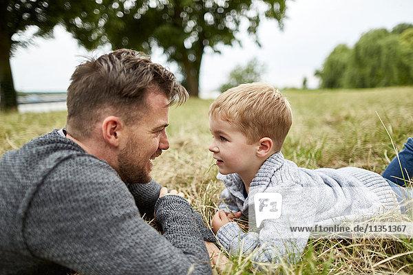 Vater und Sohn liegen auf einer Wiese und sehen sich an