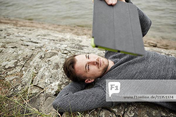 Mann liegt am Flussufer mit einem Tablet