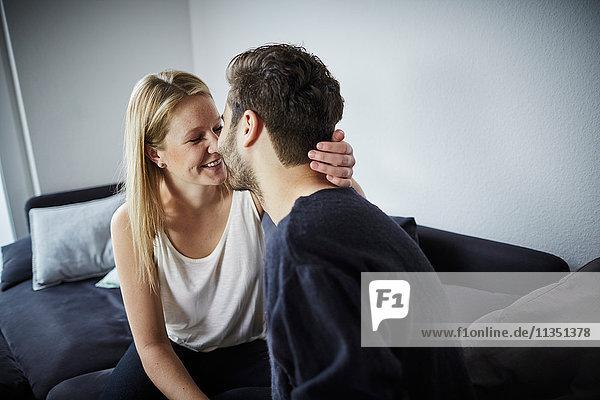 Junges Paar küsst sich auf der Couch