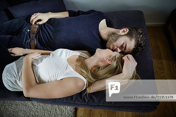 Entspanntes junges Paar liegt auf der Couch